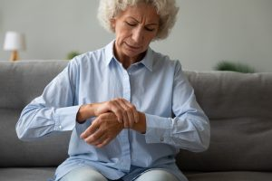 Unhappy older woman massaging wrist, feeling pain in joint